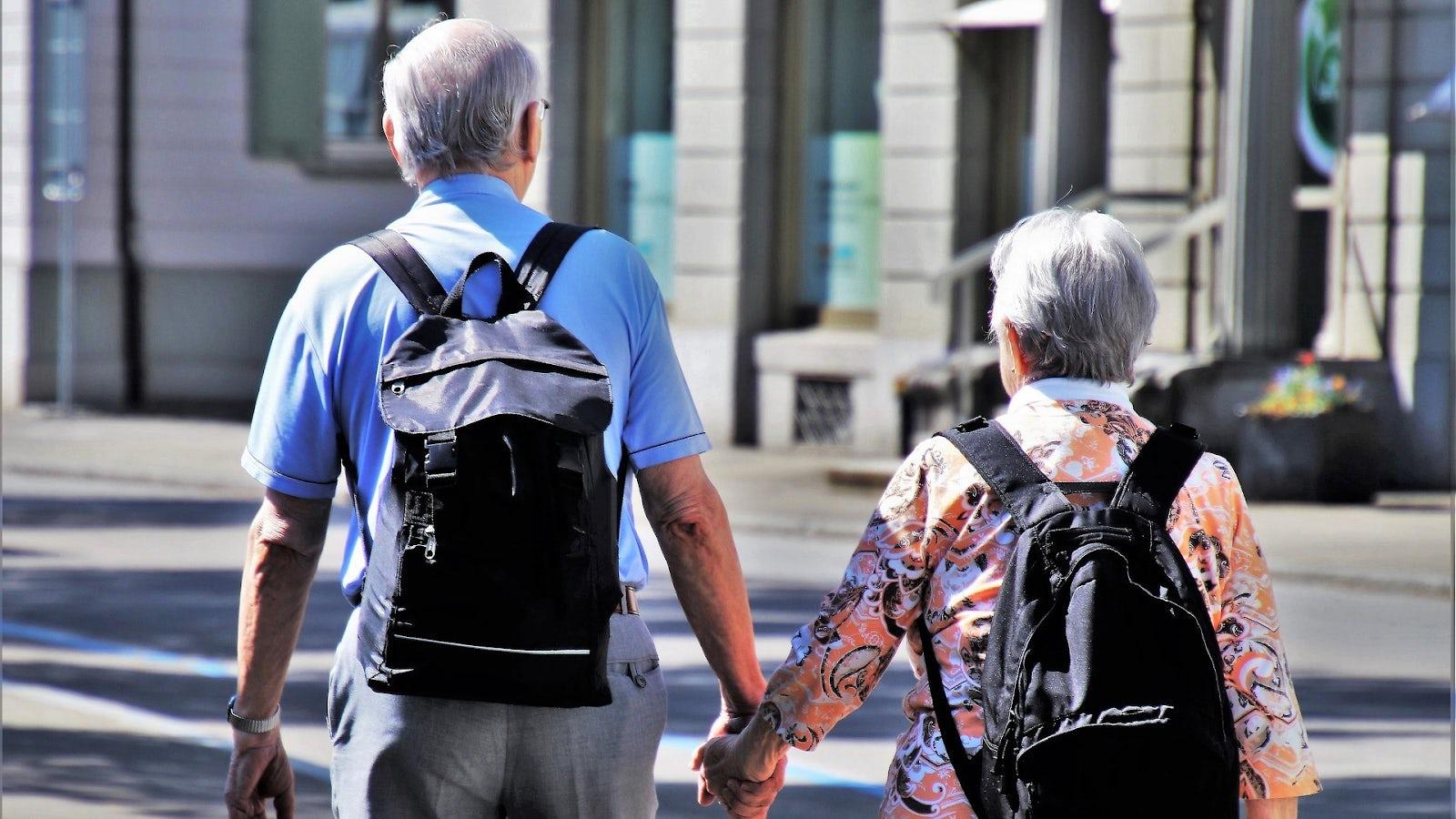 Två äldre personer som håller varandra i handen.