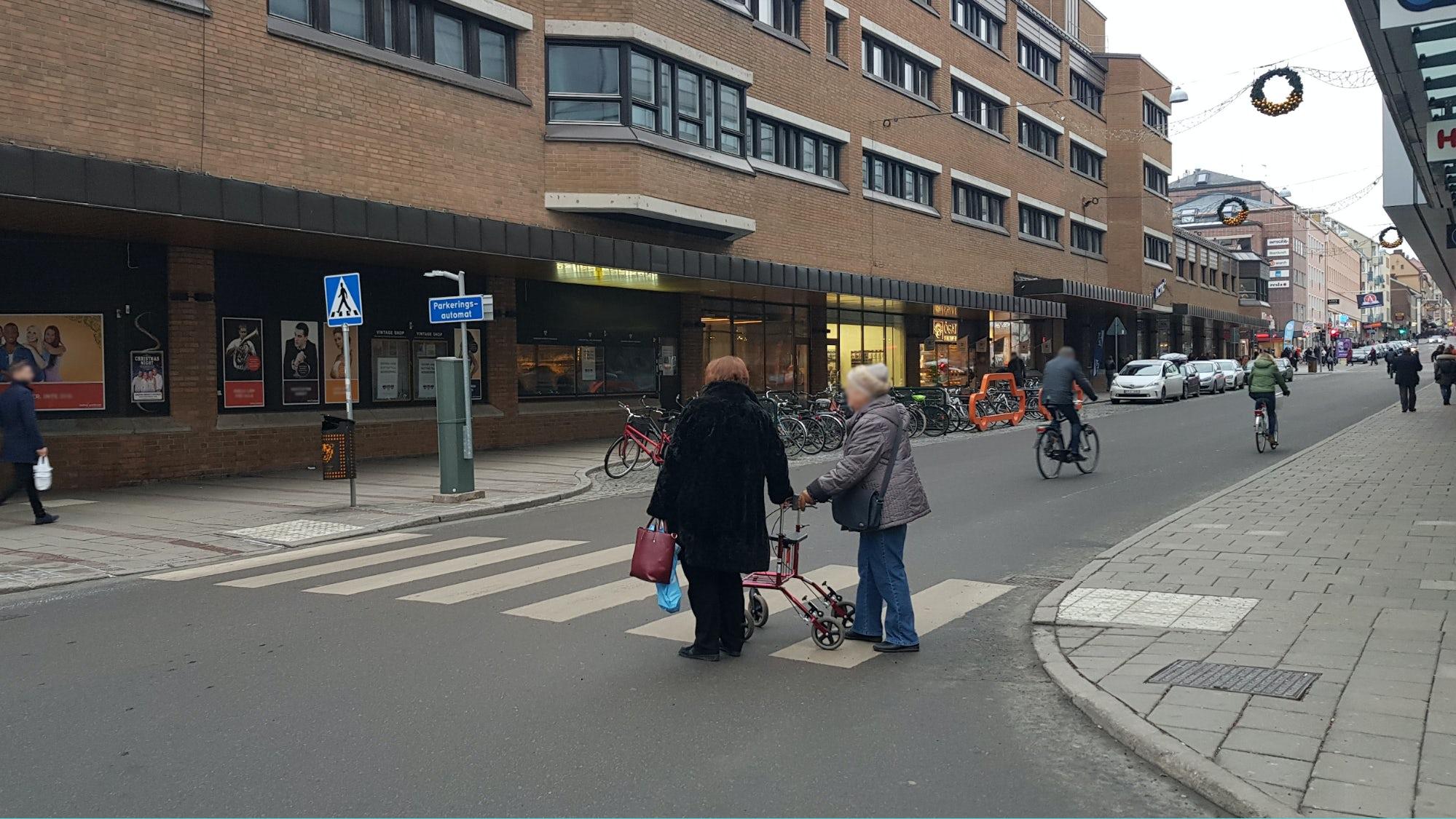 Två äldre personer med rullator går över ett övergångsställe.